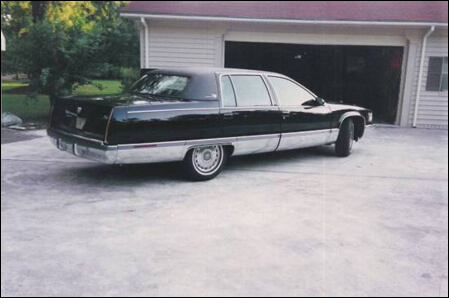 Mario's black Cadillac Fleetwood Brougham 5.7 engine, V-8, parked in the spacious driveway outside his home.