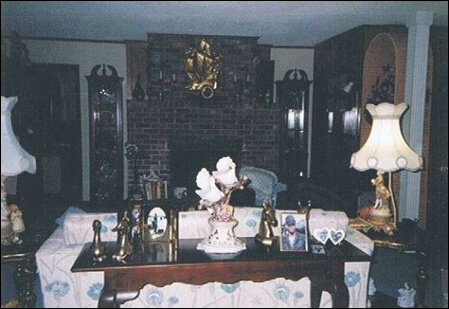 The Masellio living room, complete with Mario's hand-laid brick fireplace, a floral pattern sofa with two lamps on either side, and a table facing the door with ornaments and photographs to welcome visitors.