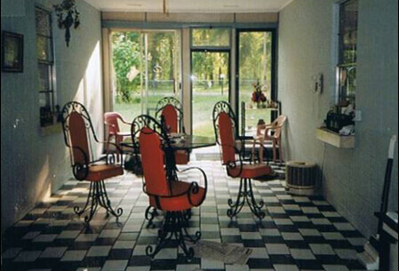 Mario's breezeway with red chairs sitting around a small table on a checkered floor.