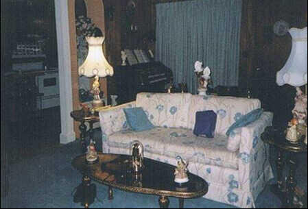 The floral sofa in Mario's living room, with two vintage lamps on either side and a coffee table.