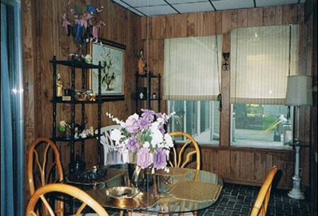 Mario's dining room. In the center, a glass table holding fresh cut flowers surrounded by vintage wooden chairs.
