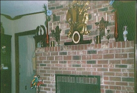 Mario's hand-laid brick fireplace. Ornamental vases line the mantelpiece, and in the center sits an ornate heirloom clock.