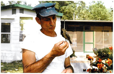 Mario Masiello holds a small bird in his hand.